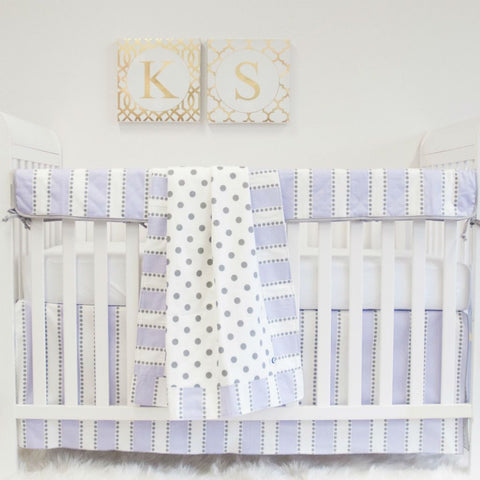 white crib with lilac purple stripe and grey and white polka dot blanket, rail protector, skirt and crib sheet