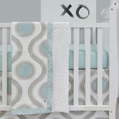 white grey and teal pattern blanket with teal circles and grey lines hanging over crib