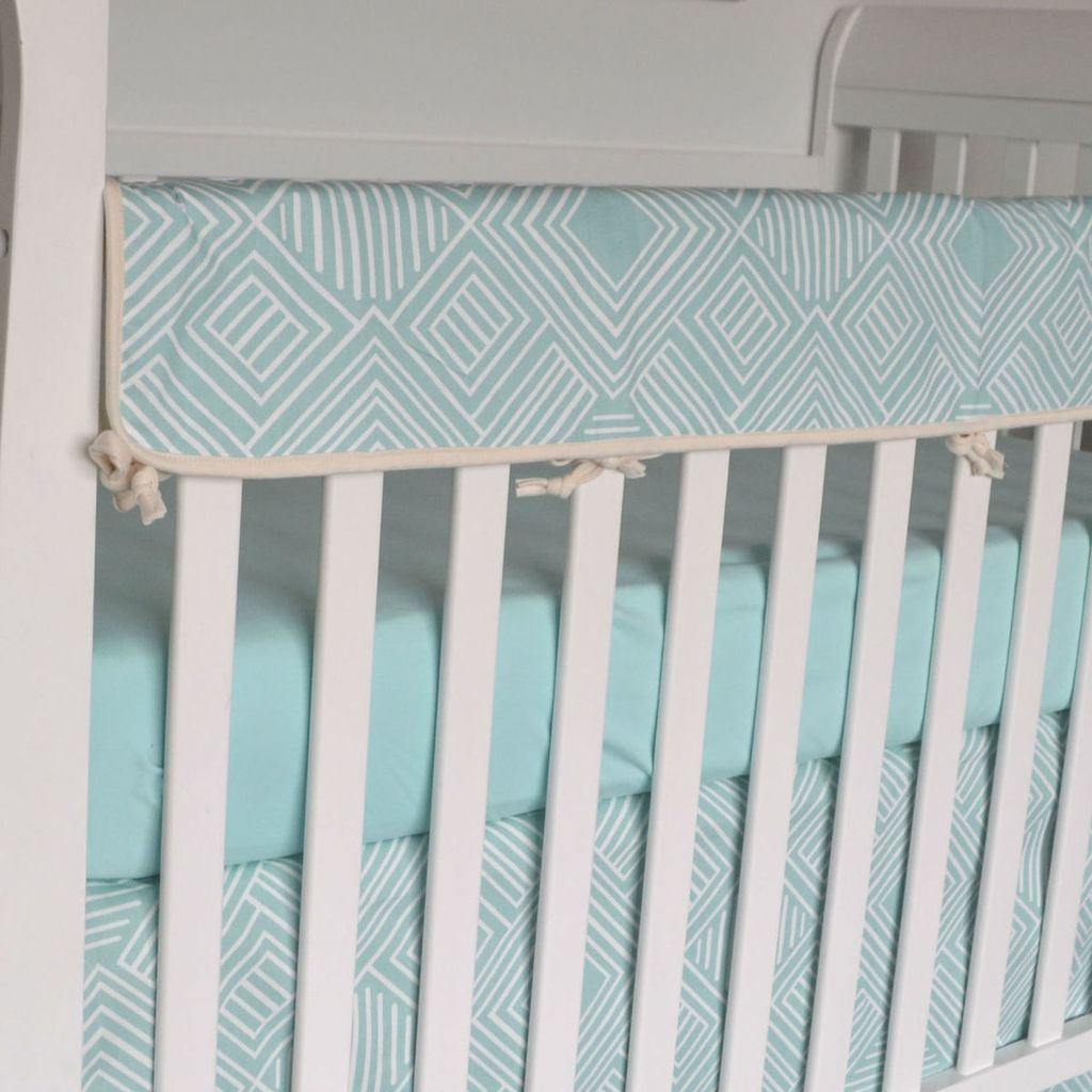 teal and white maze pattern rail protector on crib rail