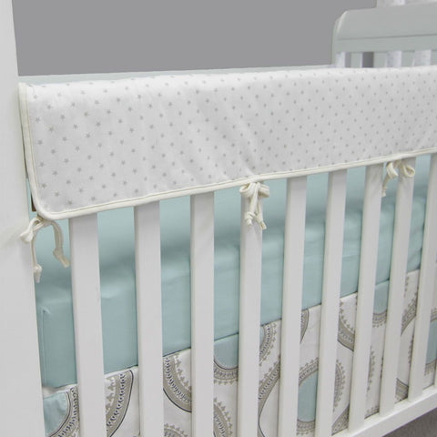 white rail protector with teal dots on aquila crib set