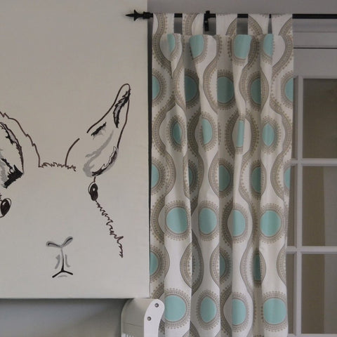 teal and grey circular pattern drapes beside bunny painting