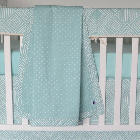 teal blanket with white dots hanging over crib with teal mattress cover and teal zig zag crib skirt