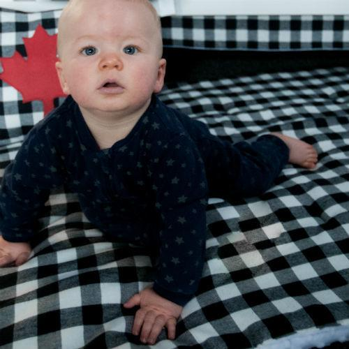 baby boy on black and white cozy plaid play blanket with maple leaf pillow