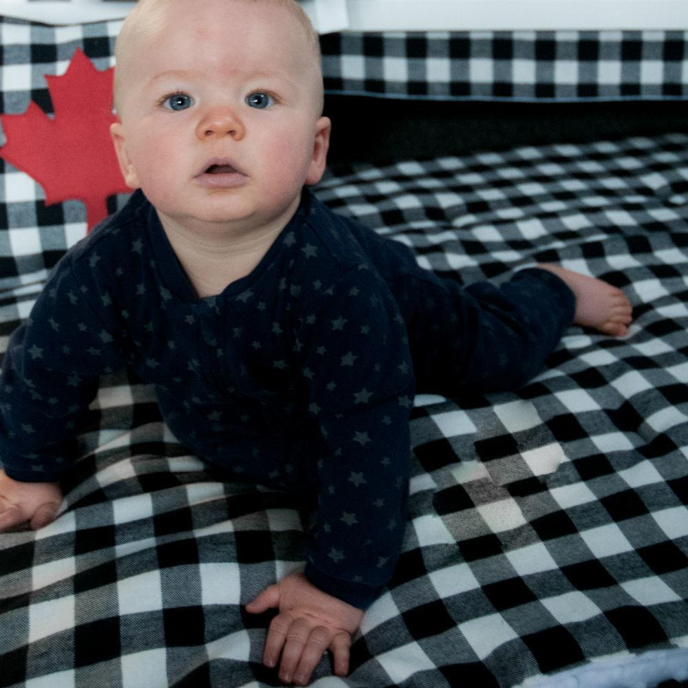 sweet baby boy on black and white plaid play blanket with maple leaf pillow