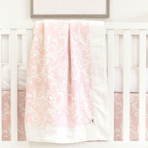 white crib with pink and white blanket, crib skirt, and white forever crib sheet