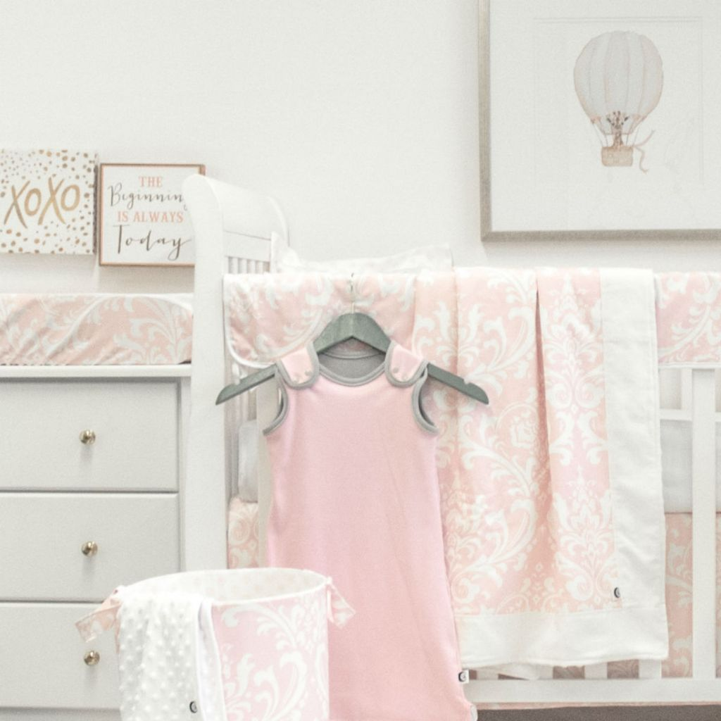white crib with pink and white blanket, rail protector, skirt, change pad cover, sleep sack, and balloon art
