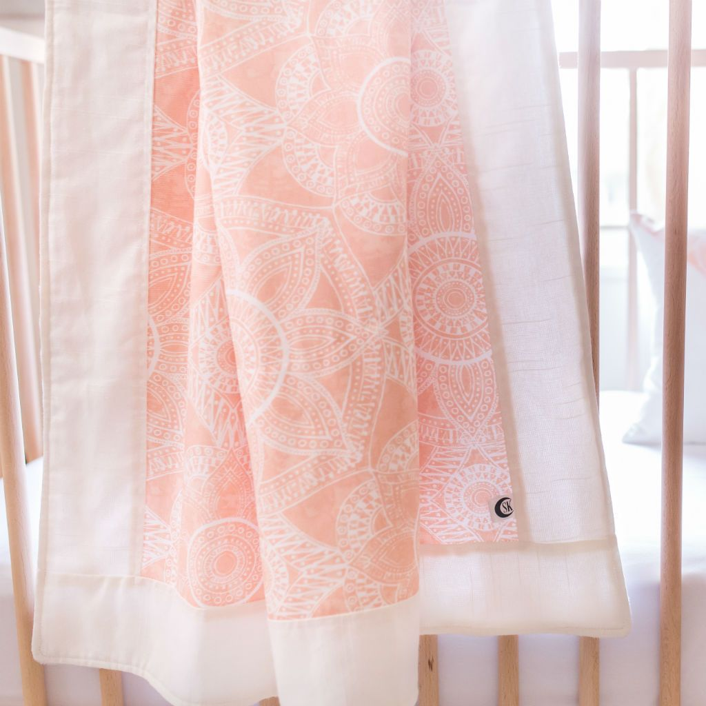 blush pink baby blanket on white crib with white sheet