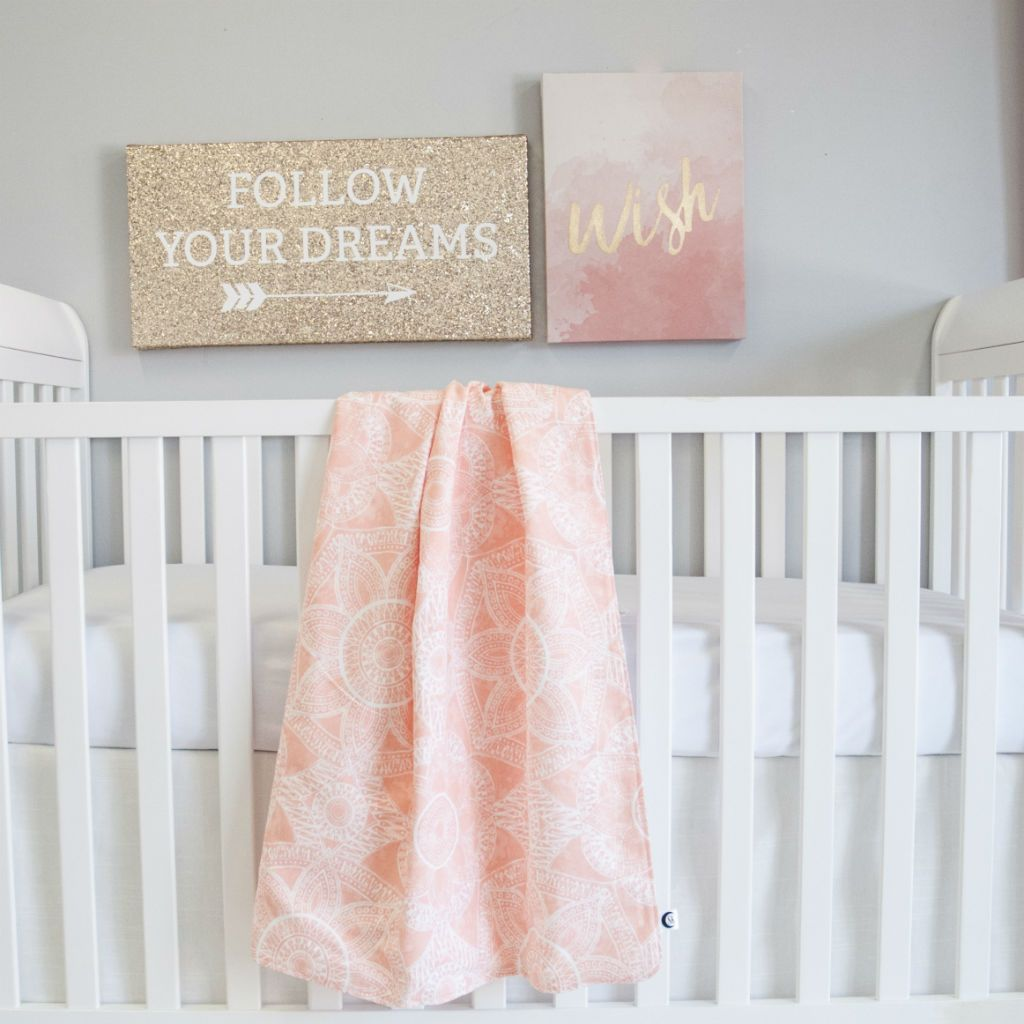 blush pink baby blanket, white crib skirt, white sheet, on white crib