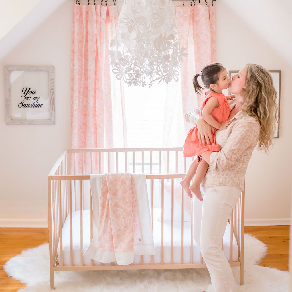 sweet toddler and mom kissing in front of wood crib and window with drapes