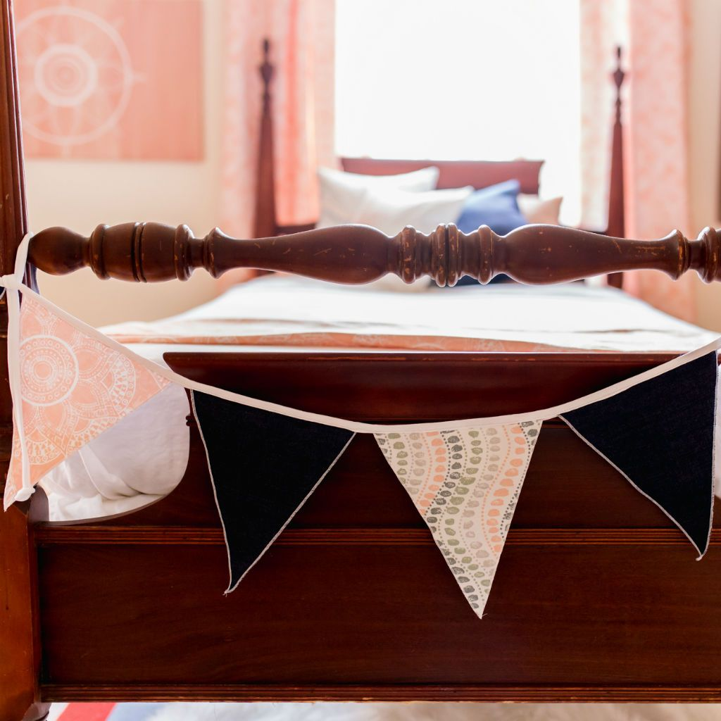 blush pink and denim varsity flags on antique wooden bed