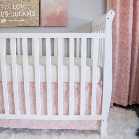 blush pink crib skirt on white crib with drapes
