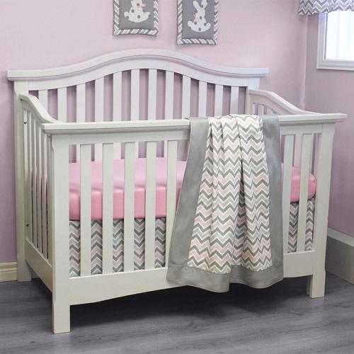white crib with grey pink and white chevron bedding