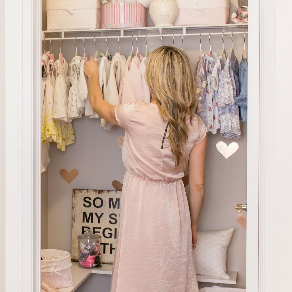 mom hanging baby clothes in closet