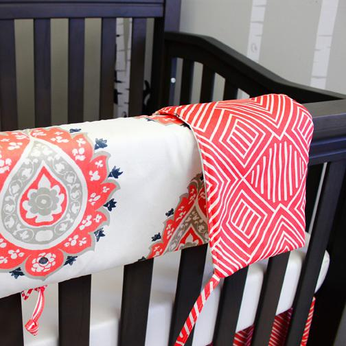 coral orange and white large paisley, and maze reversible crib rail protector, white sheet, maze skirt on grey crib