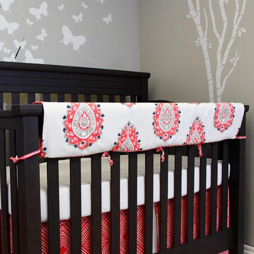 coral orange and white large paisley crib rail protector, white sheet, maze skirt on grey crib