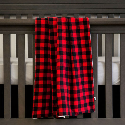 black and red plaid blanket on grey crib with grey sheet