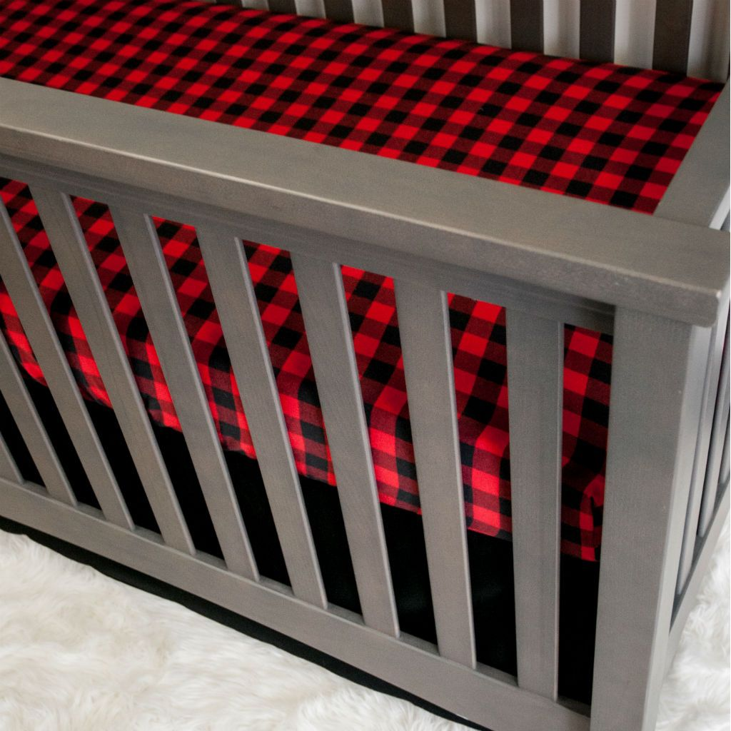 black and red plaid crib sheet with black crib skirt on grey crib