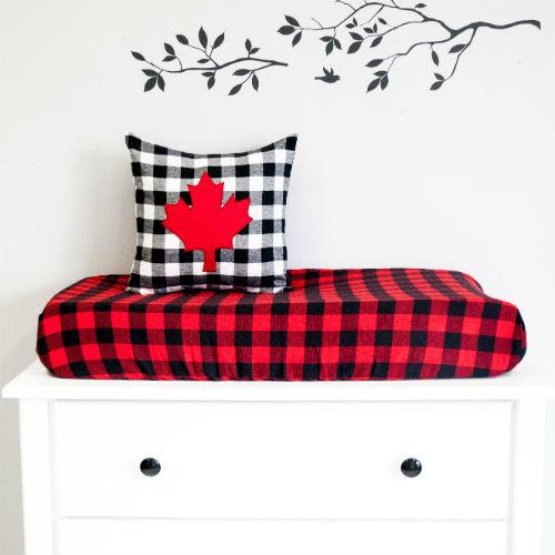black and red change pad cover with maple leaf pillow on white dresser