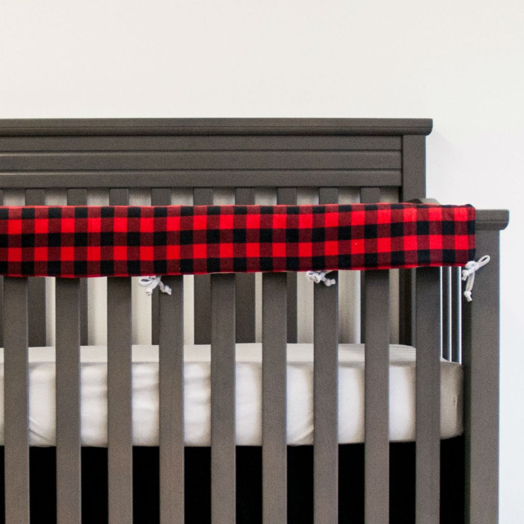 black and red plaid rail protector on grey crib with grey sheet