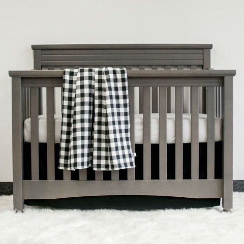 black and white plaid blanket on grey crib with grey sheet