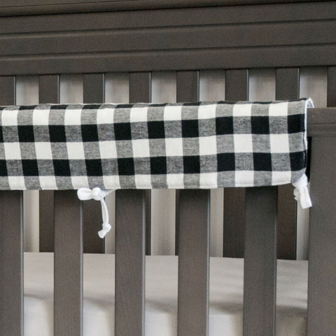 black and white plaid rail protector on grey crib with grey sheet