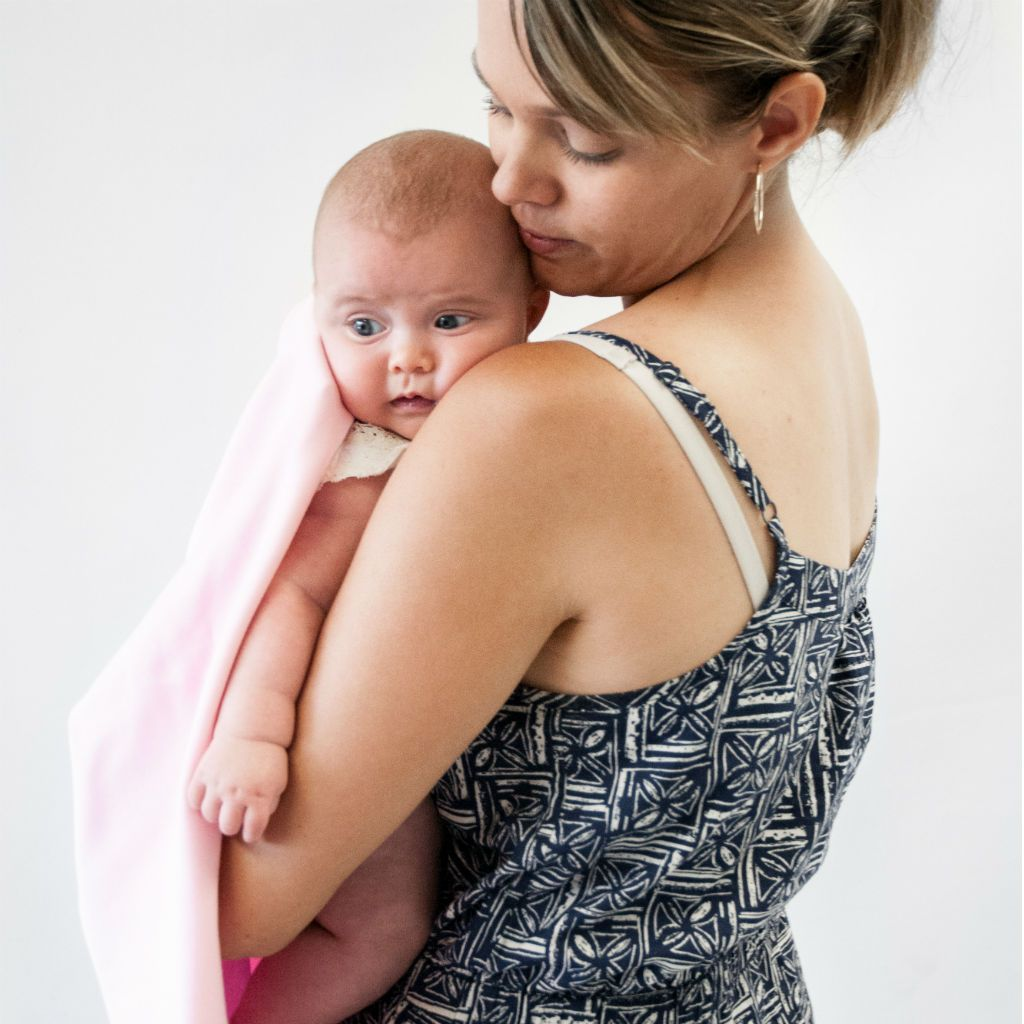 cute baby girl with mom wrapped in a pink swaddle blanket