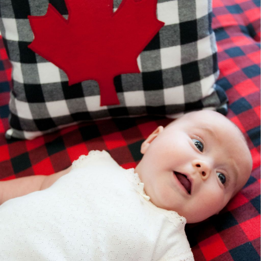 cute baby on red and black plaid crib sheet with maple-leaf pillow