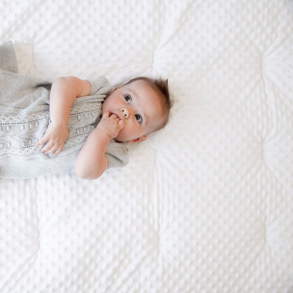 cute baby in grey dress on white minky play blanket