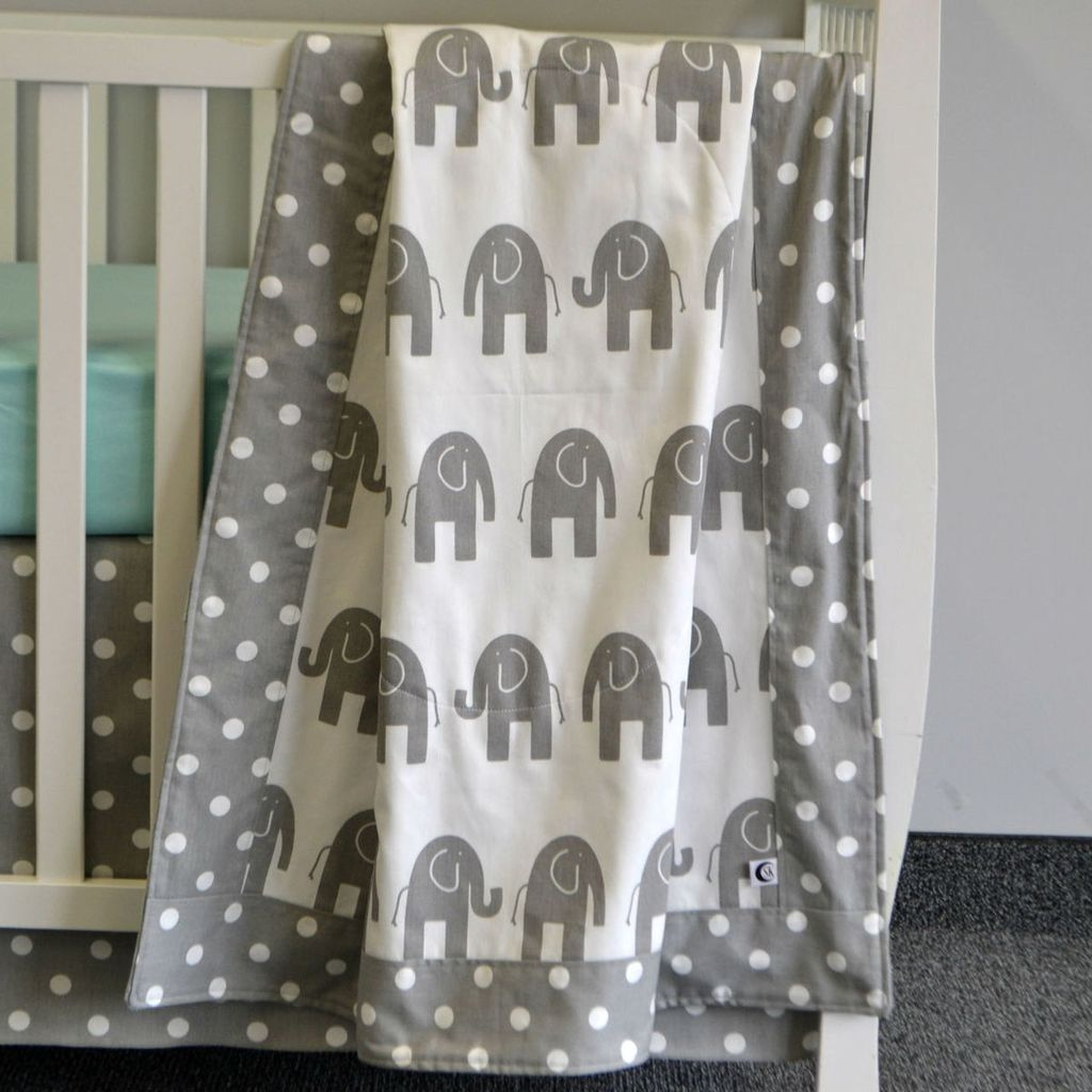 elephant baby blanket in grey and white with polka dots on white crib with aqua crib sheet