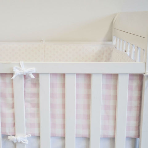 white crib with pink and white plaid and pinwheel bumper pads with forever white crib sheet