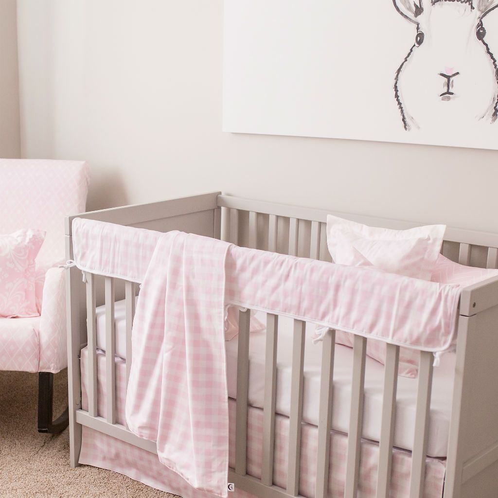 grey crib with pink and white baby blanket, rail protector, crib skirt and bunny art