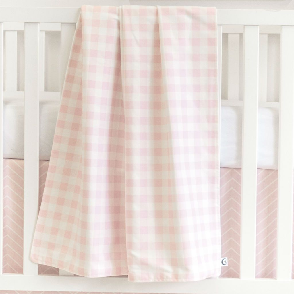 white crib with pink and white plaid baby blanket and pink chevron crib skirt with forever white crib sheet