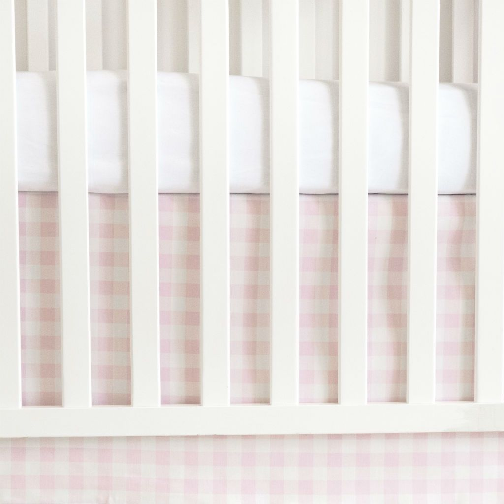 white crib with pink plaid crib skirt and white forever crib sheet