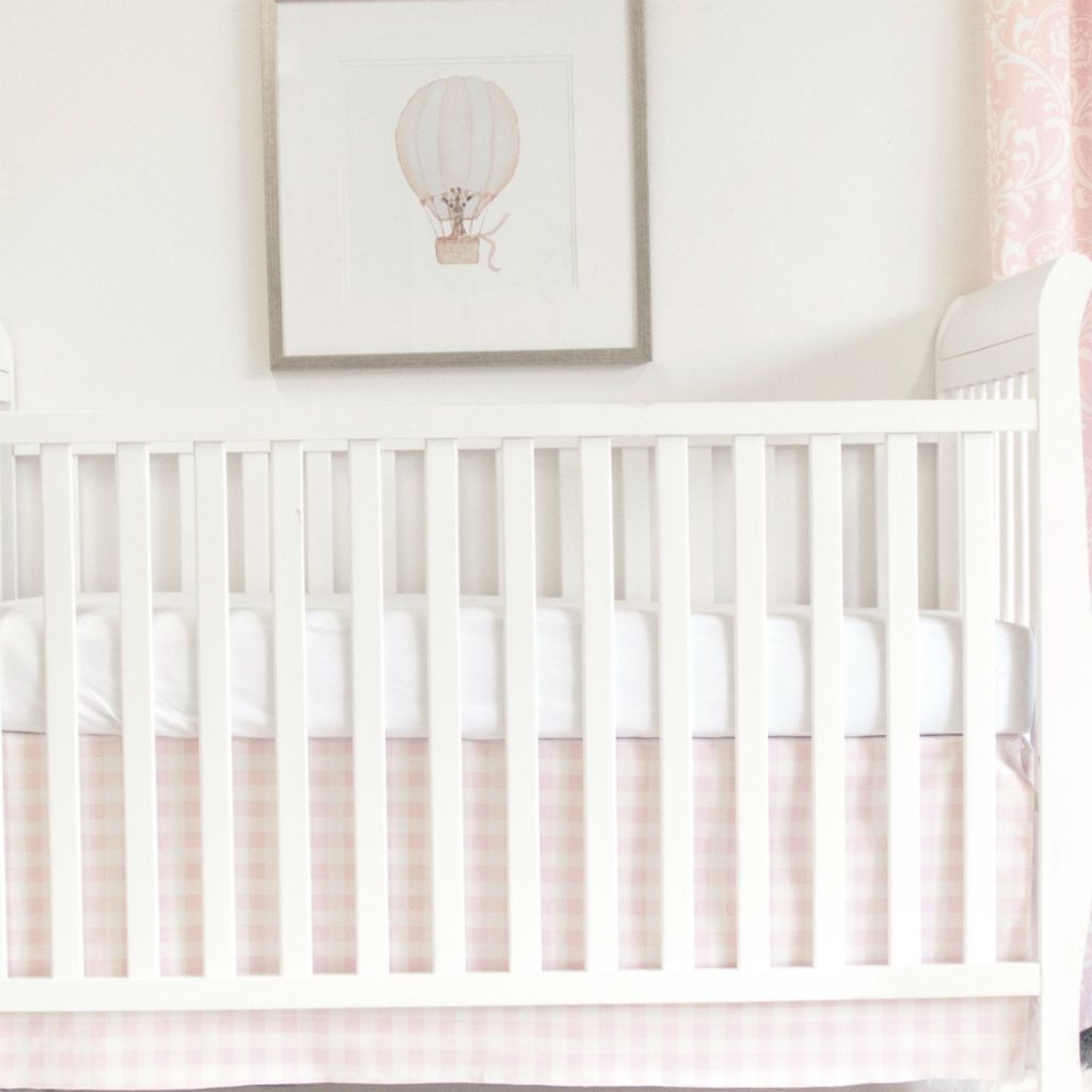 white crib with pink plaid crib skirt and white forever crib sheet, and balloon art