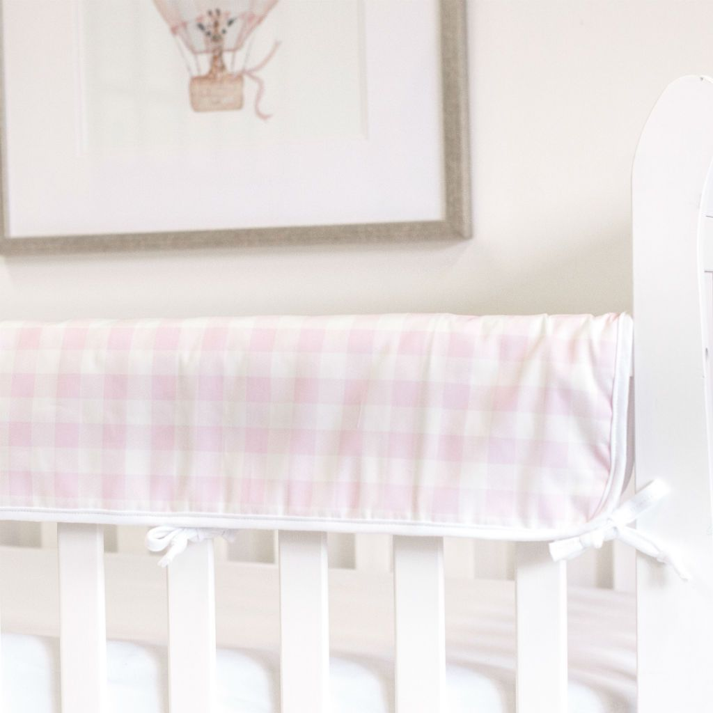 white crib with pink and white plaid rail protector and white forever crib sheet with balloon art