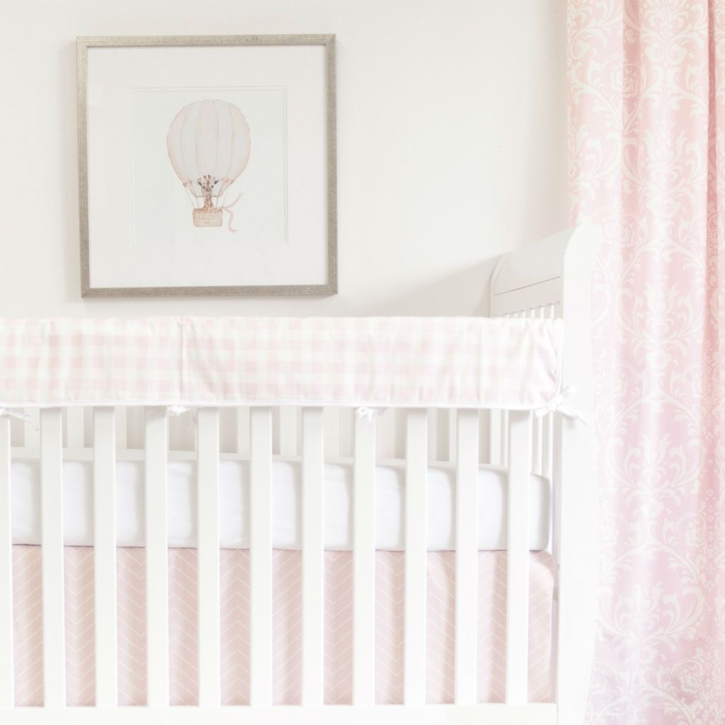 white crib with pink plaid rail protector, chevron crib skirt and white forever crib sheet, and balloon art