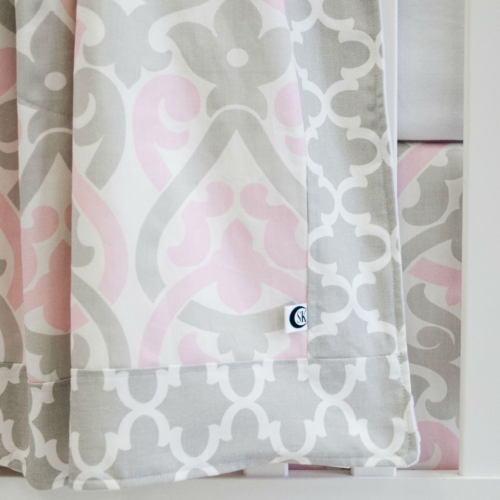 white crib with pink and grey floral scroll and grey trellis blanket, and crib skirt