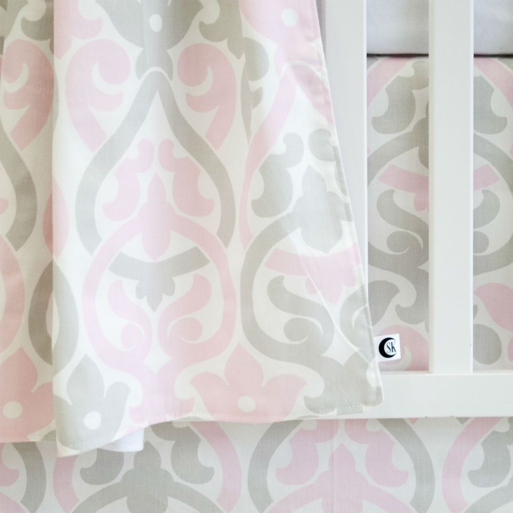 white crib with pink and grey floral scroll and grey blanket, and crib skirt