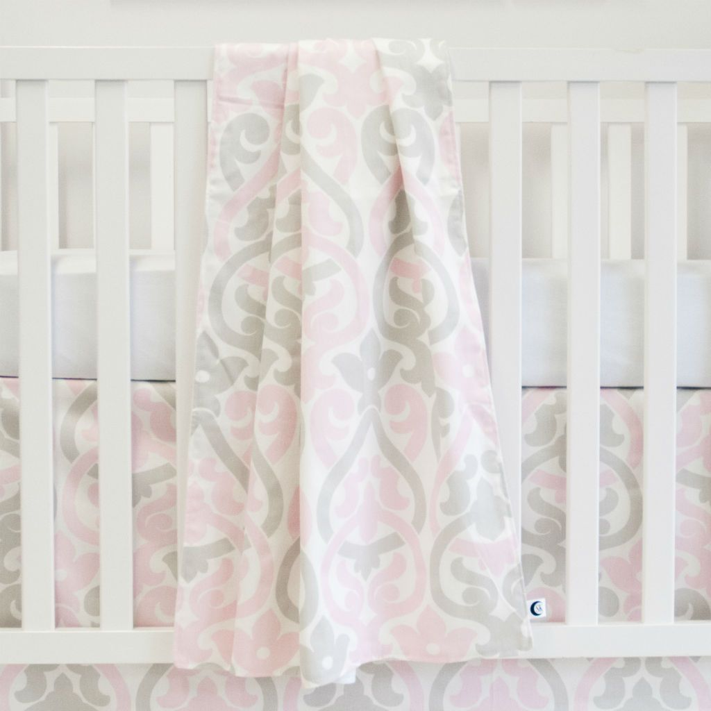 white crib with pink and grey floral scroll blanket, and crib skirt