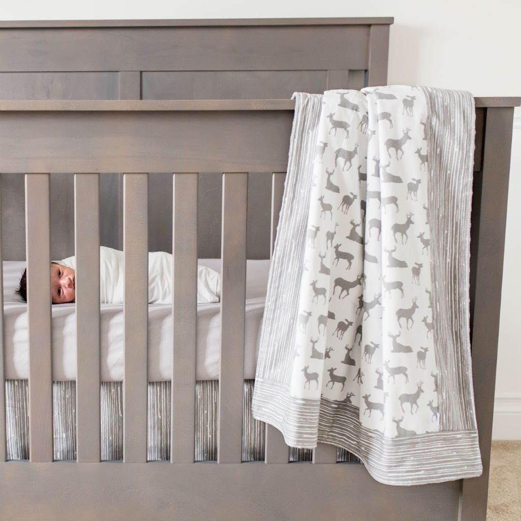 baby in crib with grey and white deer pattern blanket