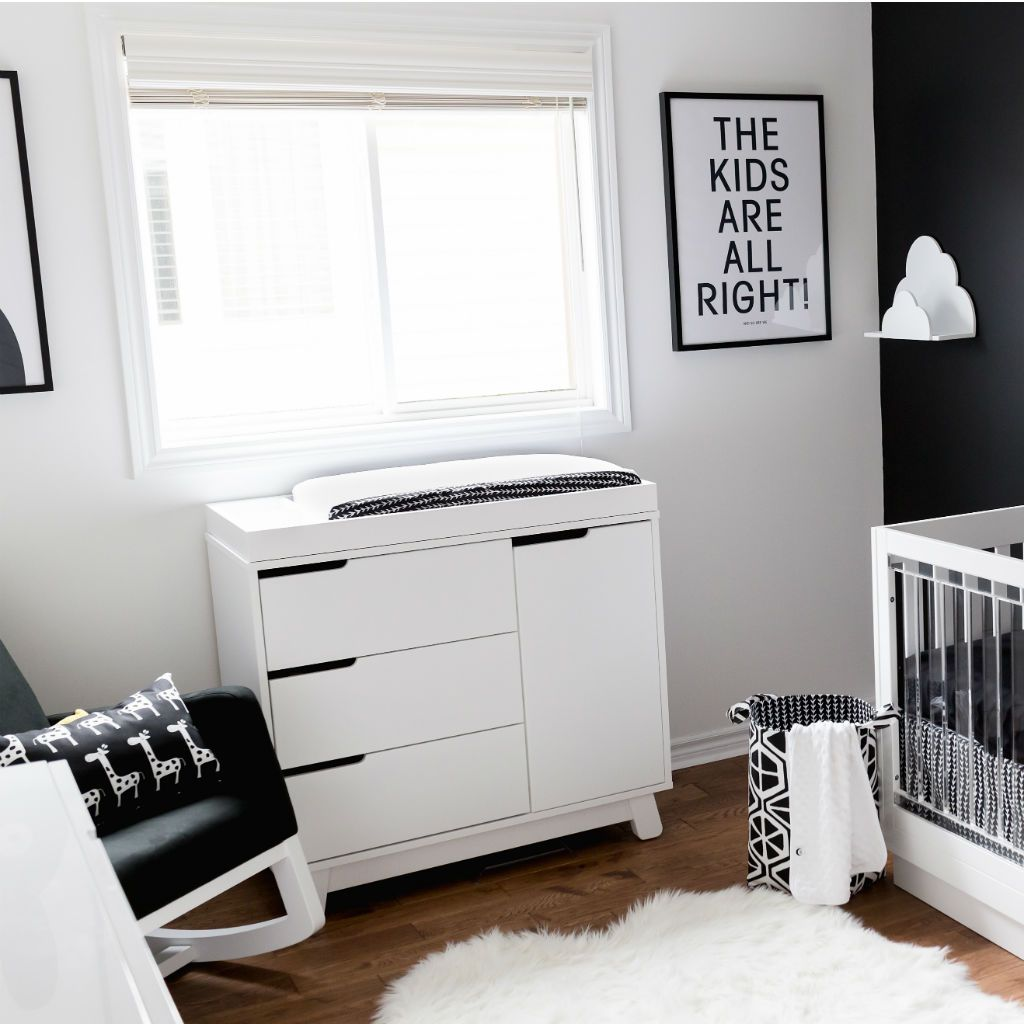 black and white nursery with change table, crib and chair