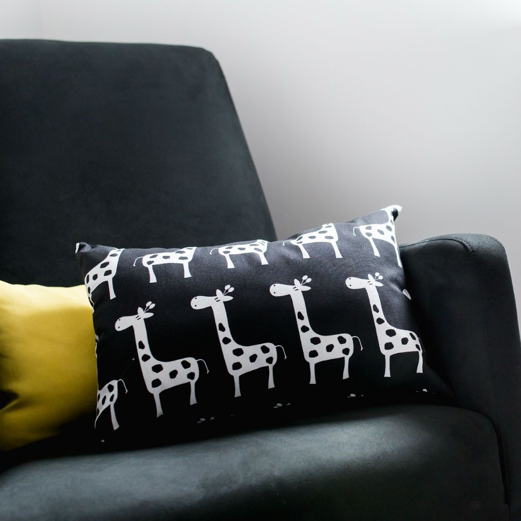 black and white giraffe lumbar pillow on a black chair with yellow accent pillow