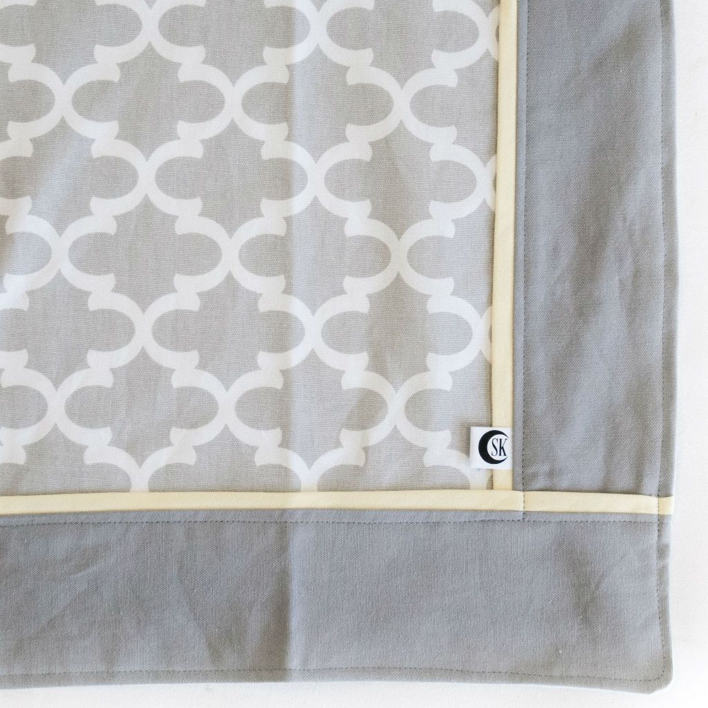 grey and white trellis baby blanket with yellow trim