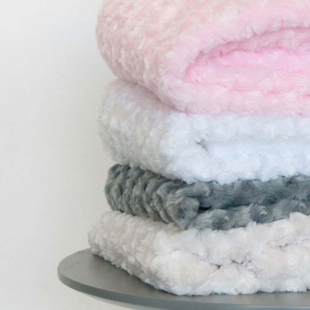 swirl chenille minky blankets in pink, white, grey, ivory on three legged table