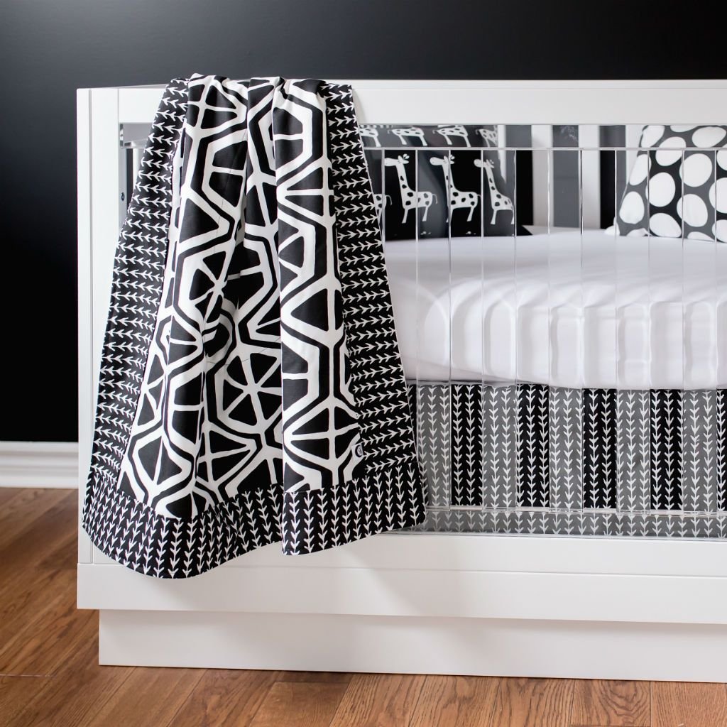 geometric black and white blanket hanging on crib with clear rails