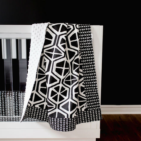 black and white geometric pattern blanket on a white crib