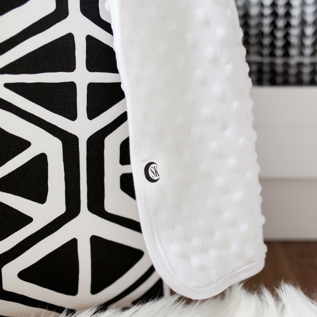 close up view of white blanket and black and white hamper