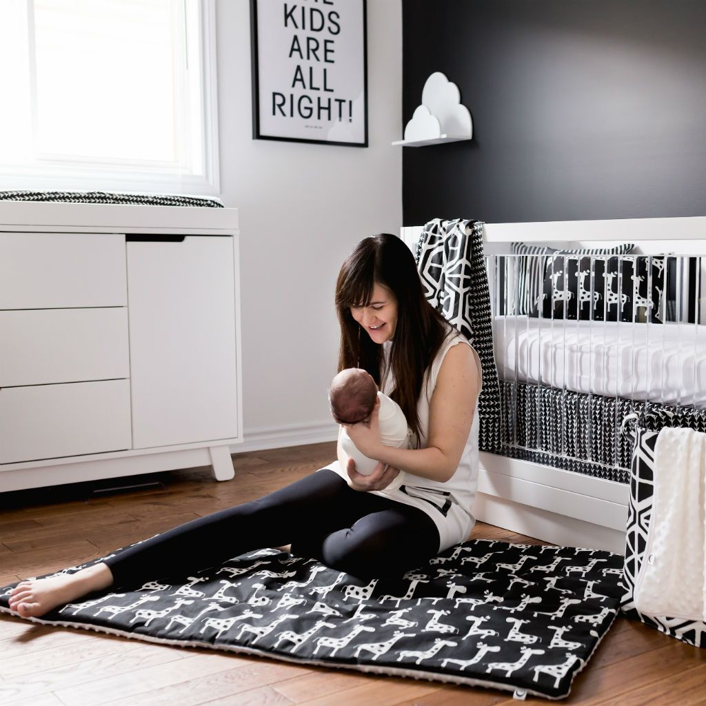 mom sitting on black and white play blanket holding baby in black and white nursery