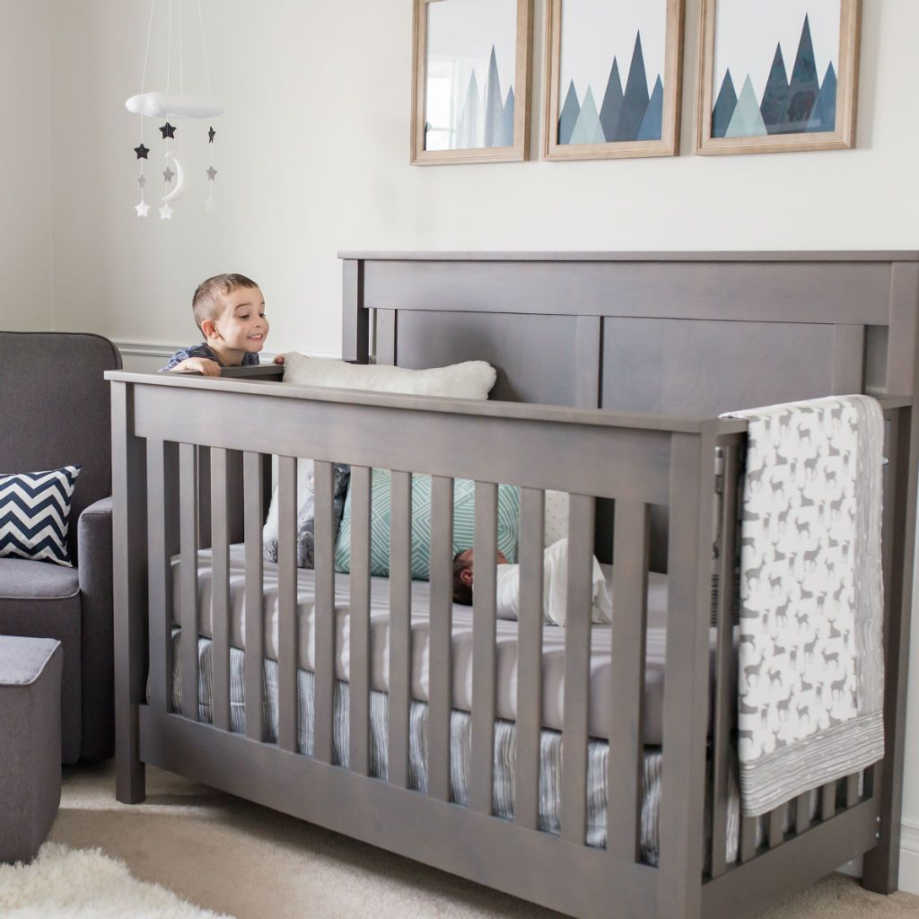 child looking into grey and white deer pattern crib set