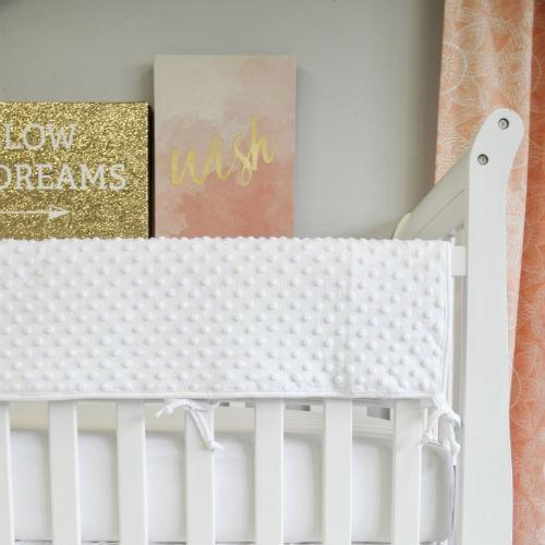 white bubble minky chenille rail protector sheet on white crib with blush pink art